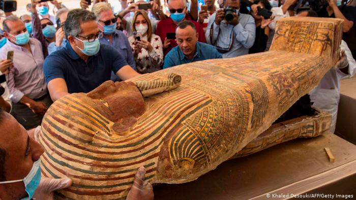 A picture taken on October 3, 2020, showing the Egyptian Minister of Tourism and Antiquities Khaled Al-Anani (left) and Mustafa Waziri (Deem), Secretary-General of the Supreme Council of Antiquities in Egypt, while opening a coffin excavated by the archaeological mission.  An Egyptian woman works at the Sakara Cemetery, 30 km south of the capital, Cairo.