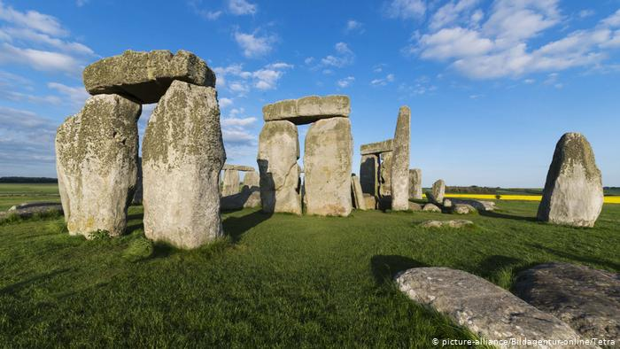 Stonehenge monuments on a green meadow.