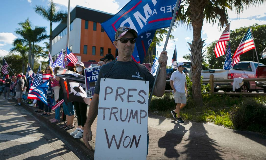 & # 034;  President Trump won [as eleições]& # 034 ;, a poster of a Donald Trump supporter waiting for the train on the way to the Mar-e-Lago Golf Club in Palm Beach, Florida, where Trump lives and stays, while Joe Biden takes office Washington Photo: EVA MARIE UZCATEGUI / AFP