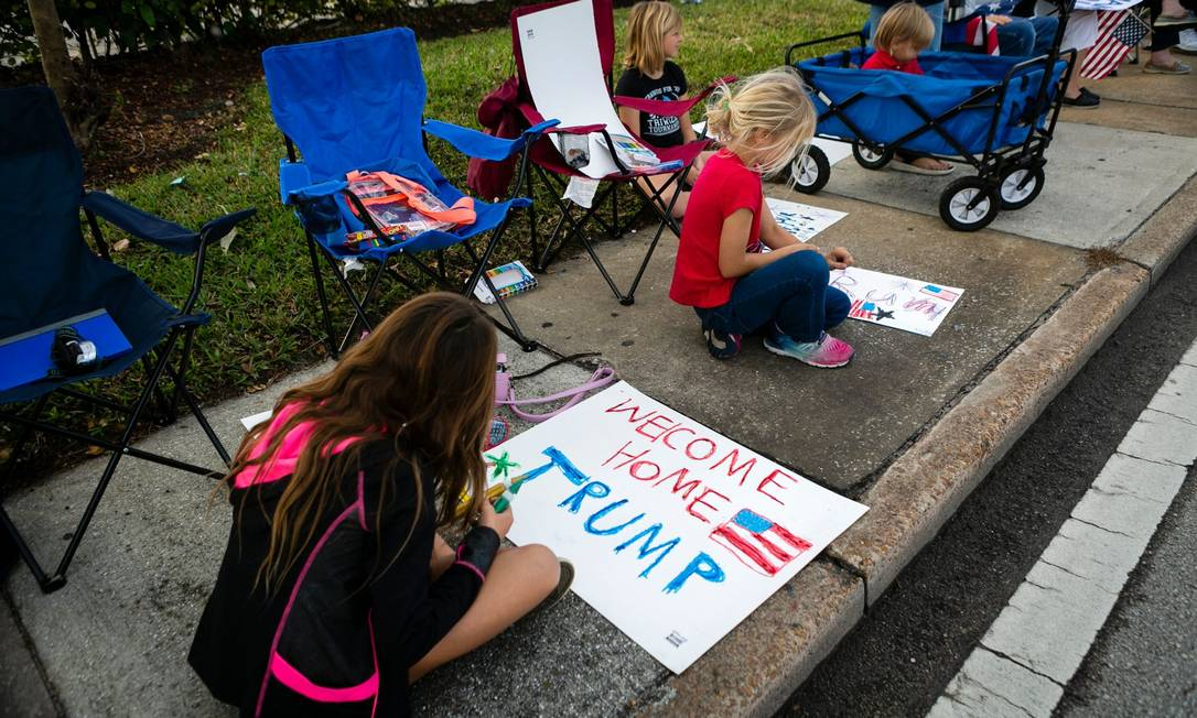 Children of Donald Trump supporters paint posters for an event as they pass by the entourage of Donald Trump supporters who decided not to attend the inauguration of elected political opponent Joe Biden, and spend time with his family at home in Mar-A-Logo Golf Club in Palm Beach, Florida A / G
