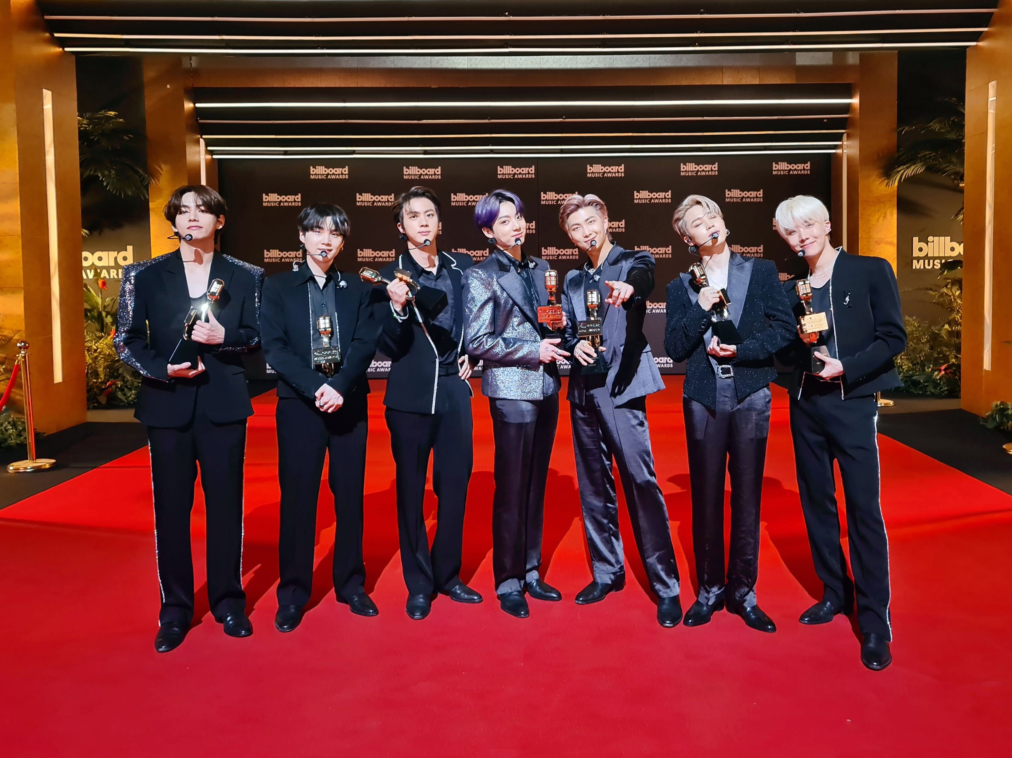 Seven members of BTS on the red carpet at the Billboard Music Awards 2021;  They are aligned horizontally, each holding a prize in a bold dress