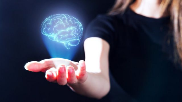 A woman with an illustration of a brain in her hand.