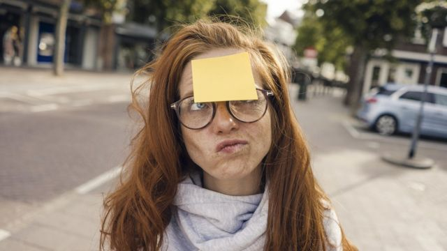 Woman holding blank sticky notes on her forehead