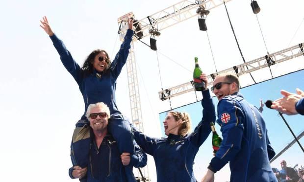 Richard Branson carries Virgin Galactic Vice President Sirisha Bandla on his shoulders and celebrates with the team Photo: PATRICK T. FALLON / AFP