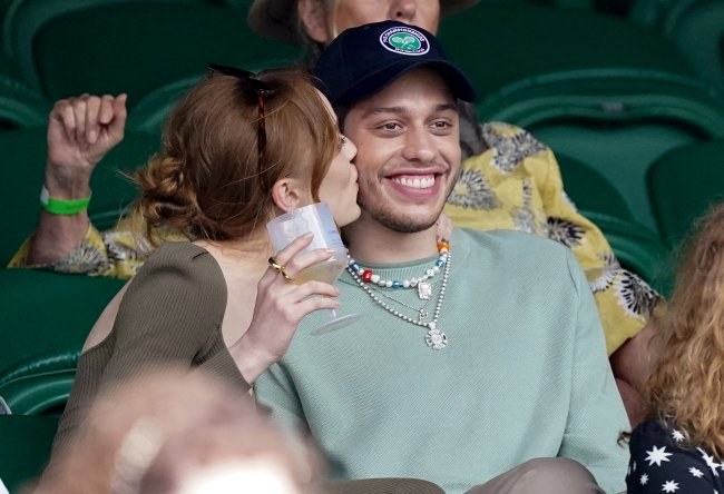 Phoebe Denivore kisses Pete Davidson on the cheek, who smiles widely.