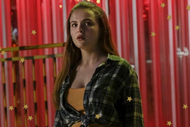 Focusing on the face of Janet's character, from the Cruel Summer series, she looks to the side with a serious expression in an orange plaid shirt.