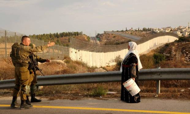 A Palestinian woman talks to an IDF military man in his olive fields on the other side of the Israeli separation wall, after he obtained special Israeli permission to pick olive trees in Hebron, West Bank, Photo: Hazem Bader/AFP