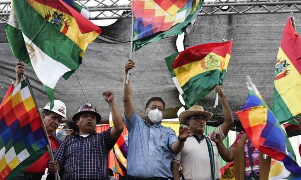 Bolivian President Luis Arres, wearing a mask, waves the Wipala flag - which represents the indigenous peoples of the Andes - during a pro-government rally in Santa Cruz, Bolivia. Photo: AIZAR RALDES / AFP